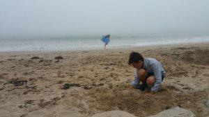 Kind buddelt bei Regen am Strand