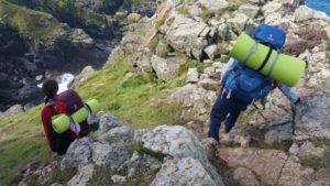 Kinder klettern mit Rucksäcken über Felsen