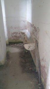 Eine Waschrinne, gegenüber zwei Toiletten.
